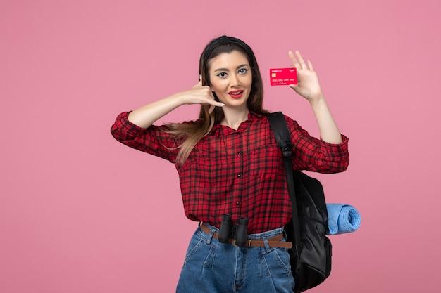 Vooraanzicht jonge vrouw in rood shirt met bankkaart op de roze achtergrond menselijke vrouw kleur