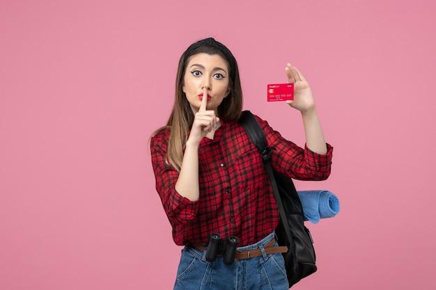 Vooraanzicht jonge vrouw in rood shirt met bankkaart op de roze achtergrond vrouw kleur mens