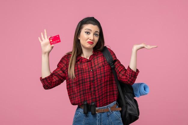 Vooraanzicht jonge vrouw in rood shirt met bankkaart op roze achtergrond kleur vrouw mens