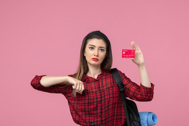 Vooraanzicht jonge vrouw in rood shirt met bankkaart op roze achtergrond menselijke vrouw kleur