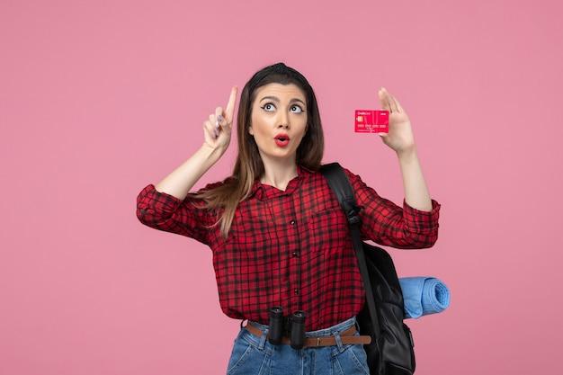 Vooraanzicht jonge vrouw in rood shirt met bankkaart op roze achtergrond menselijke vrouw kleuren