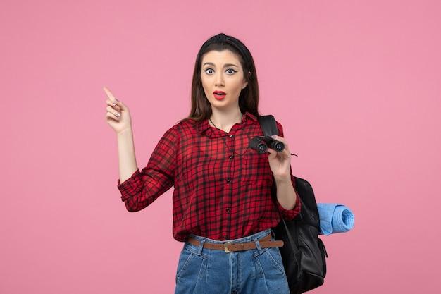 Vooraanzicht jonge vrouw in rood shirt met een verrekijker op de roze achtergrond vrouw kleur student