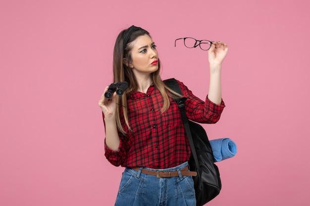 Vooraanzicht jonge vrouw in rood shirt met een verrekijker op het roze achtergrondmodel van de vrouwenfoto