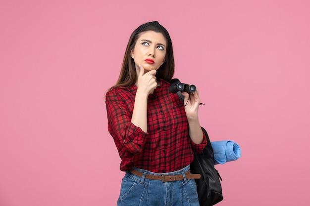 Vooraanzicht jonge vrouw in rood shirt met een verrekijker op roze achtergrond kleur studente