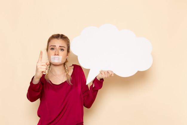 Vooraanzicht jonge vrouw in rood shirt met gebonden mond huilen met wit bord op de crème ruimte vrouwelijk doek geweld