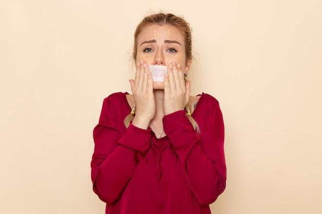 Vooraanzicht jonge vrouw in rood shirt met gebonden mond huilen op de crème ruimte vrouwelijk doek foto geweld