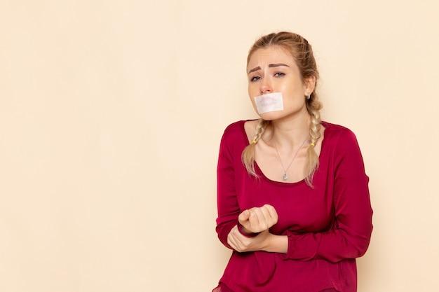 Vooraanzicht jonge vrouw in rood shirt met gebonden mond huilen op de lichte ruimte vrouwelijk doek foto geweld