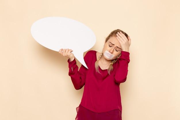 Vooraanzicht jonge vrouw in rood shirt met gebonden mond met wit bord depressief op de crème vloer vrouwelijke doek foto