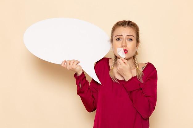 Vooraanzicht jonge vrouw in rood shirt met gebonden mond met wit bord op de crème ruimte vrouwelijke doek foto geweld huiselijk