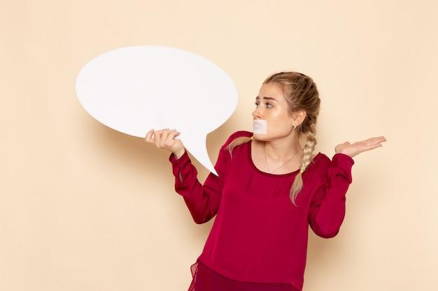 Vooraanzicht jonge vrouw in rood shirt met gebonden mond met wit bord op de foto van de crème ruimte vrouwelijke doek