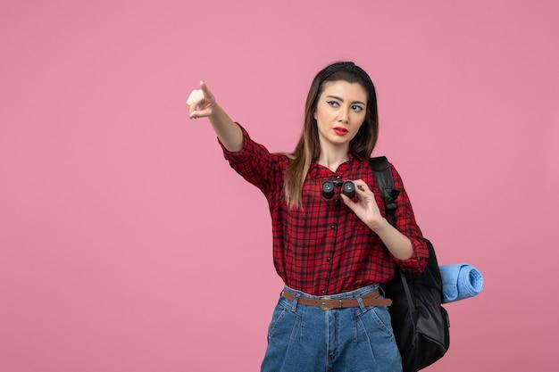 Vooraanzicht jonge vrouw in rood shirt met verrekijker op de roze achtergrond kleur menselijke vrouw