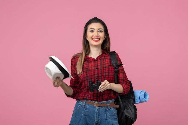Vooraanzicht jonge vrouw in rood shirt met verrekijker op de roze achtergrondkleur vrouw mens