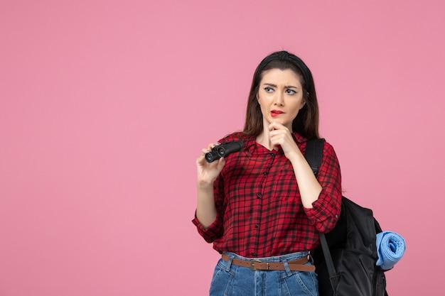 Vooraanzicht jonge vrouw in rood shirt met verrekijker op een roze bureau student kleur vrouw