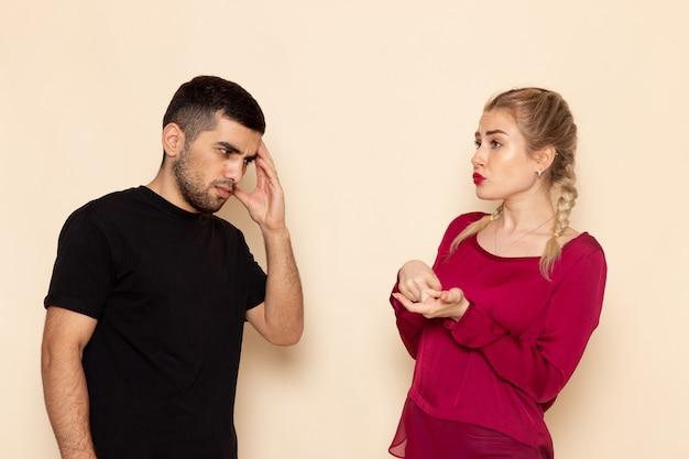 Vooraanzicht jonge vrouw in rood shirt quarelling met jonge man op de crème ruimte vrouwelijke doek confrontatie