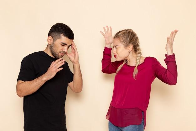 Vooraanzicht jonge vrouw in rood shirt quarelling met jonge man op de crème ruimte vrouwelijke doek foto