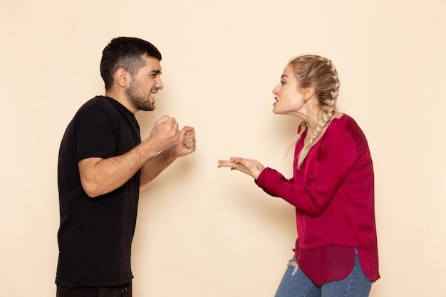 Vooraanzicht jonge vrouw in rood shirt quarelling met jonge man op de crème ruimte vrouwelijke doek quarell