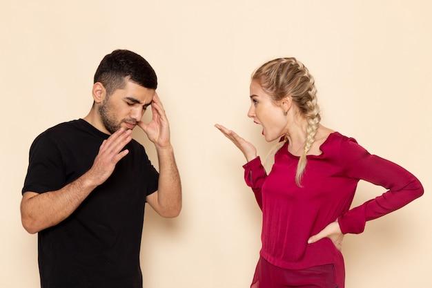 Vooraanzicht jonge vrouw in rood shirt quarelling met jonge man op de foto van de lichte ruimte vrouwelijke doek