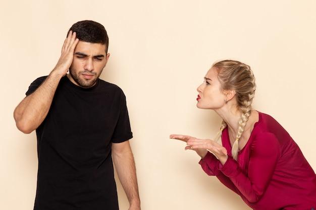 Vooraanzicht jonge vrouw in rood shirt quarelling met man op de crème ruimte vrouwelijke doek foto geweld