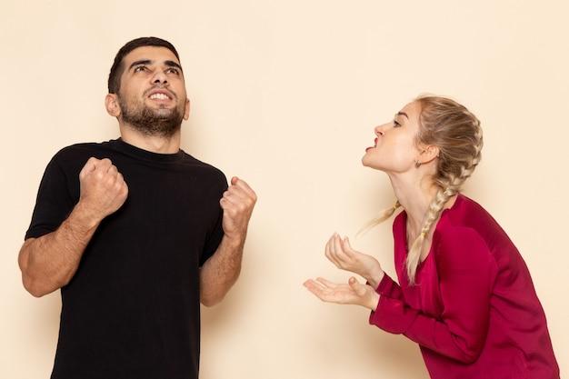 Vooraanzicht jonge vrouw in rood shirt quarelling met man op de foto van de crème ruimte vrouwelijke doek