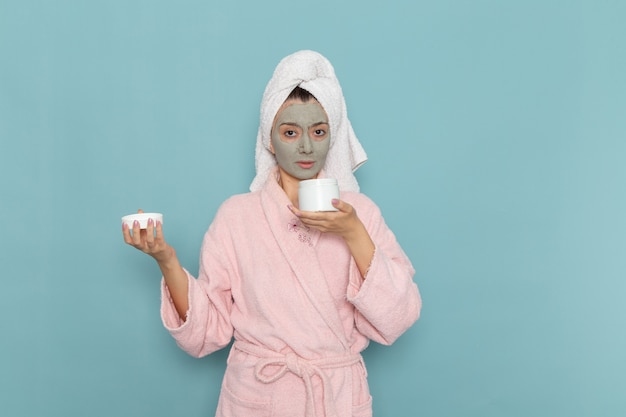 Vooraanzicht jonge vrouw in roze badjas met masker op haar gezicht met crème op het blauwe bureau douche schoonmakende schoonheid zelfzorgcrème