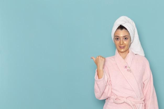 Vooraanzicht jonge vrouw in roze badjas na douche lachend op blauwe muur schoonheid water crème zelfzorg douche badkamer