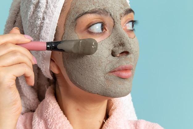 Vooraanzicht jonge vrouw in roze badjas na douche masker toepassen op het blauwe oppervlak