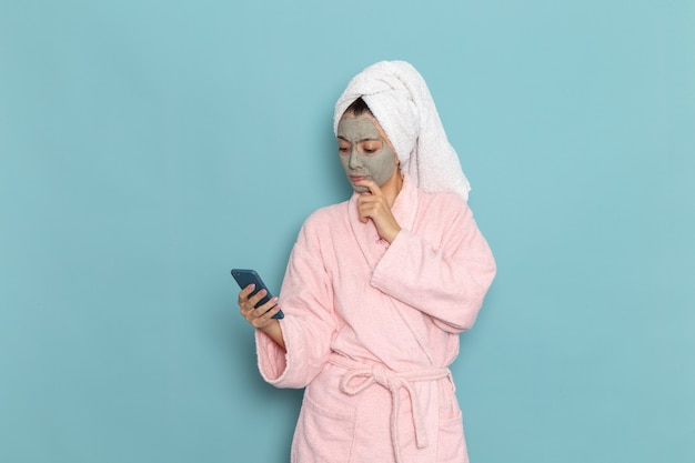 Vooraanzicht jonge vrouw in roze badjas na douche met behulp van haar telefoon op lichtblauwe muur schoonheid water zelfzorg douche schoon