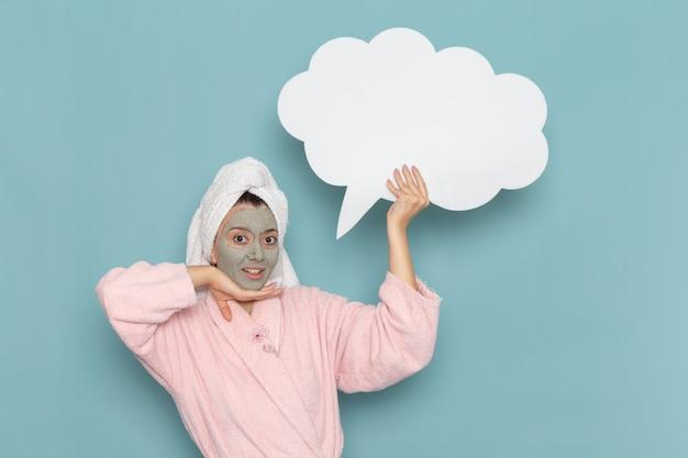 Vooraanzicht jonge vrouw in roze badjas na douche met wit bordje op lichtblauwe muur schoonheid water zelfzorg douche schoon