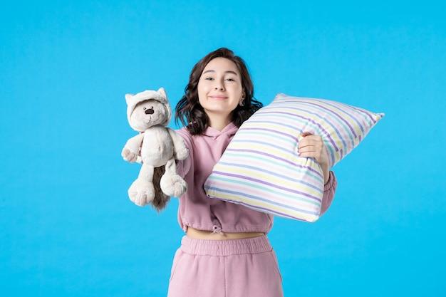 Vooraanzicht jonge vrouw in roze pyjama met kleine speelgoedbeer en kussen op blauw bed nacht feest droom nachtmerrie slaap vrouw slapeloosheid