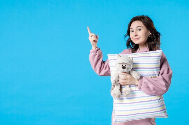 Vooraanzicht jonge vrouw in roze pyjama met kleine speelgoedbeer en kussen op blauw bed nacht nachtmerrie slaap vrouw rust slapeloosheid dromen feest