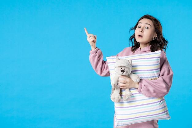 Vooraanzicht jonge vrouw in roze pyjama met kleine speelgoedbeer en kussen op blauw vrouwenbed nachtrust slapeloosheid droomfeest slaap