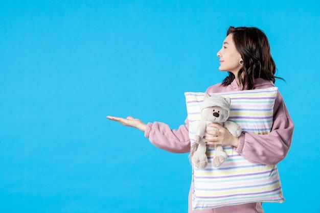 Vooraanzicht jonge vrouw in roze pyjama met kleine speelgoedbeer en kussen op blauwe slapeloosheid vrouw bed nacht nachtmerrie droom feest rust slaap