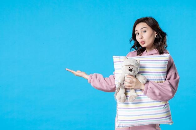 Vooraanzicht jonge vrouw in roze pyjama met kleine speelgoedbeer en kussen op blauwe vrouw bed nacht slapeloosheid droom feest rust slaap