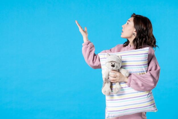 Vooraanzicht jonge vrouw in roze pyjama met kleine speelgoedbeer en kussen op blauwe vrouw