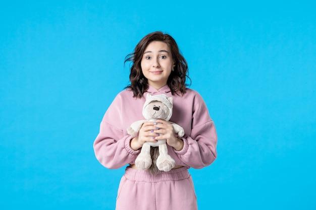 Vooraanzicht jonge vrouw in roze pyjama met kleine speelgoedbeer op blauw