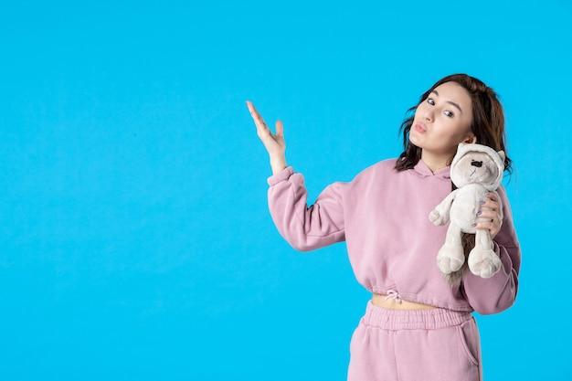 Vooraanzicht jonge vrouw in roze pyjama met kleine speelgoedbeer op blauwe dromenkleur