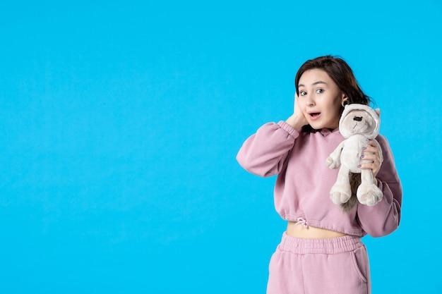 Vooraanzicht jonge vrouw in roze pyjama met kleine speelgoedbeer op blauwe droom