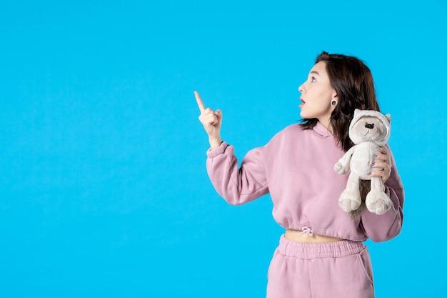 Vooraanzicht jonge vrouw in roze pyjama met kleine speelgoedbeer op blauwe droomkleur nacht slaap bed vrouw partij slapeloosheid