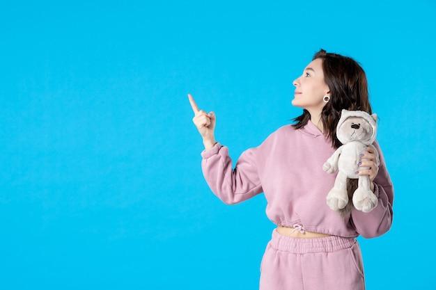 Vooraanzicht jonge vrouw in roze pyjama met kleine speelgoedbeer op blauwe droomkleur nacht slaap bed vrouw rust slapeloosheid