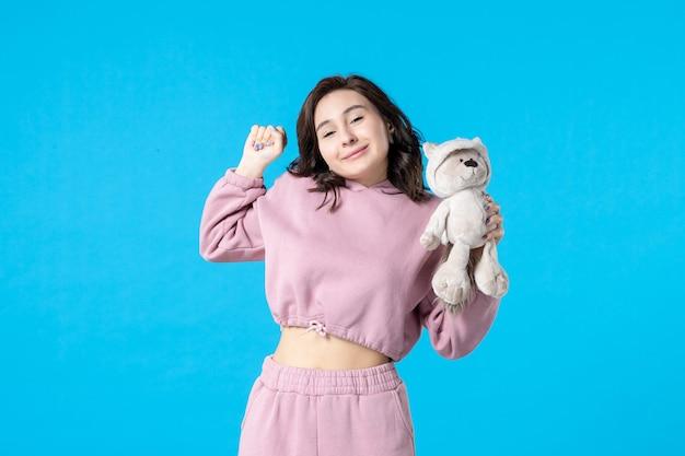 Vooraanzicht jonge vrouw in roze pyjama met kleine speelgoedbeer op blauwe droomkleur nacht slaap slapeloosheid bed vrouw feest