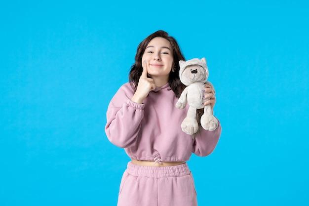 Vooraanzicht jonge vrouw in roze pyjama met kleine speelgoedbeer op blauwe droomkleur nachtslaap bed vrouw feestrust