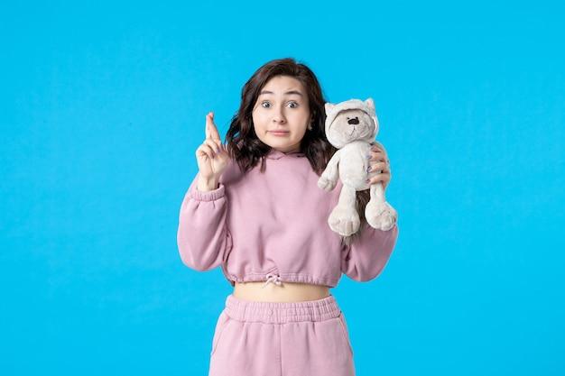 Vooraanzicht jonge vrouw in roze pyjama met kleine speelgoedbeer op blauwe droomkleur