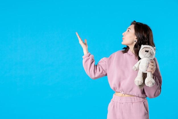Vooraanzicht jonge vrouw in roze pyjama met kleine speelgoedbeer op blauwe droomkleuren