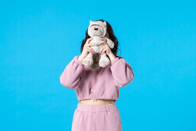 Vooraanzicht jonge vrouw in roze pyjama met kleine speelgoedbeer op blauwe kleur nacht slaap slapeloosheid droom bed vrouw feest rust
