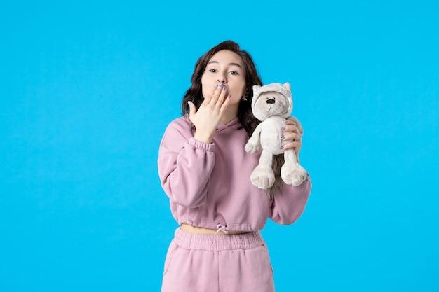 Vooraanzicht jonge vrouw in roze pyjama met kleine speelgoedbeer op blauwe kleur nacht slaap slapeloosheid droom bed vrouw rust
