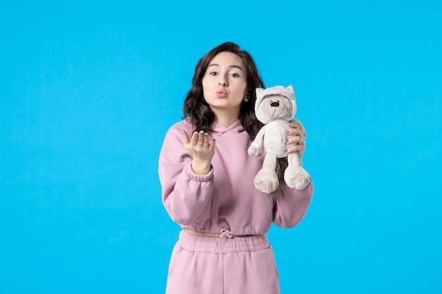 Vooraanzicht jonge vrouw in roze pyjama met kleine speelgoedbeer op blauwe kleur nachtrust slapeloosheid droom bed vrouw feest rust kus