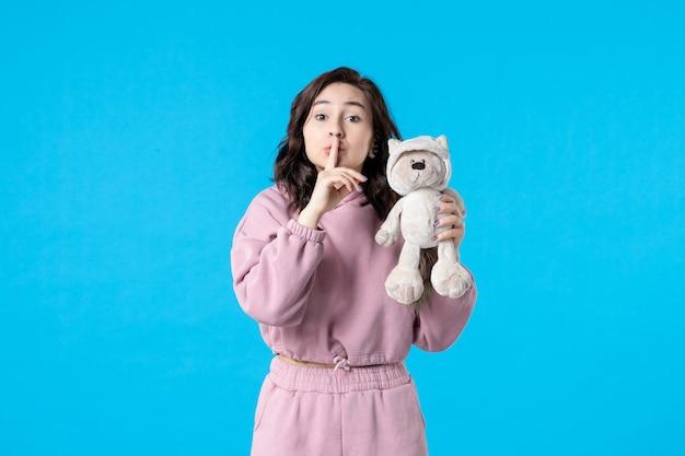 Vooraanzicht jonge vrouw in roze pyjama met kleine speelgoedbeer op blauwe kleur nachtrust slapeloosheid droom bed vrouw feest rust rustig