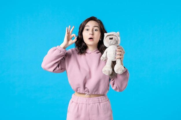 Vooraanzicht jonge vrouw in roze pyjama met kleine speelgoedbeer op blauwe kleur nachtrust slapeloosheid droomvrouw feestrust