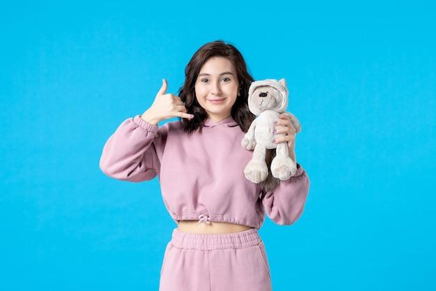 Vooraanzicht jonge vrouw in roze pyjama met kleine speelgoedbeer op blauwe kleur