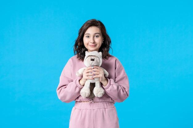 Vooraanzicht jonge vrouw in roze pyjama met kleine speelgoedbeer op blauwe nachtkleur feest slaap droom rust bed vrouw